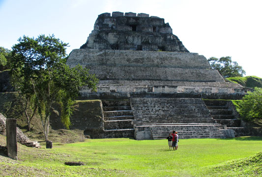 Xunantunich Ruins, central pyramid, guide holds court in golden midday sunshine.